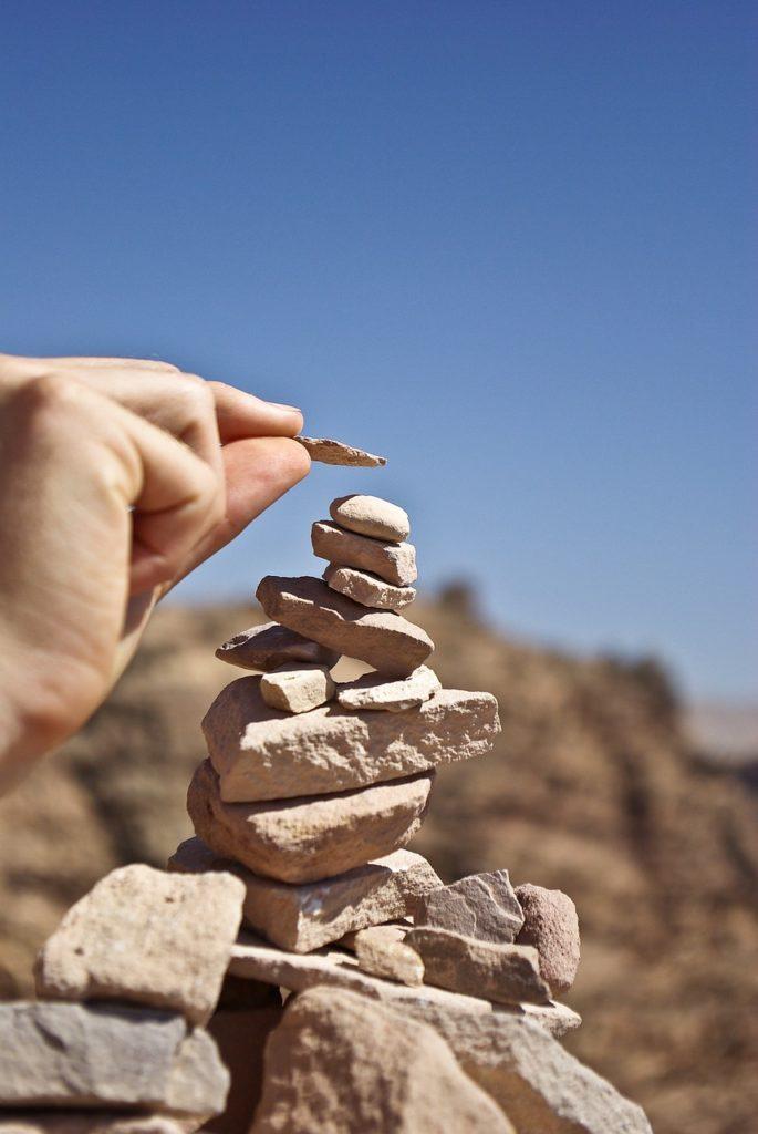 Försiktigt placera en sten på ett stenröse